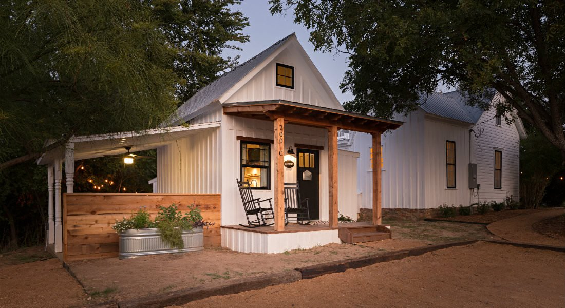 white cottage at dusk with covered front porch and covered side patio with privacy wall