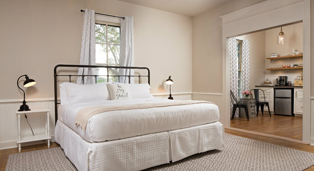 Spacious beige room with wood floors, metal bed dressed in white with matching nightstands and gooseneck lamps