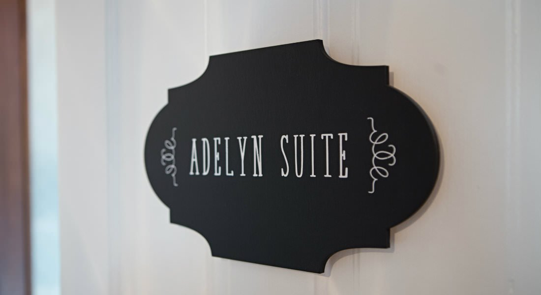 close-up view of black oval Adelyn Suite sign