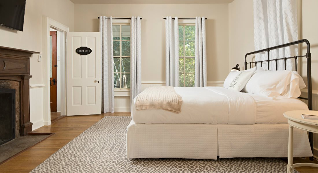 Beige room with wood floors, large area rug, several windows, white dressed bed and fireplace