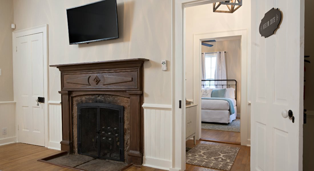 Flat screen TV hanging over stained wood fireplace surround with glimpse of bedroom through hall in the background