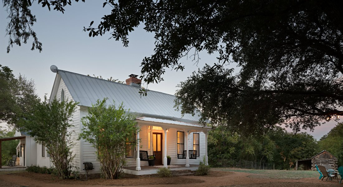 White cottage warmly lit at dusk with covered front porch and two porch swings