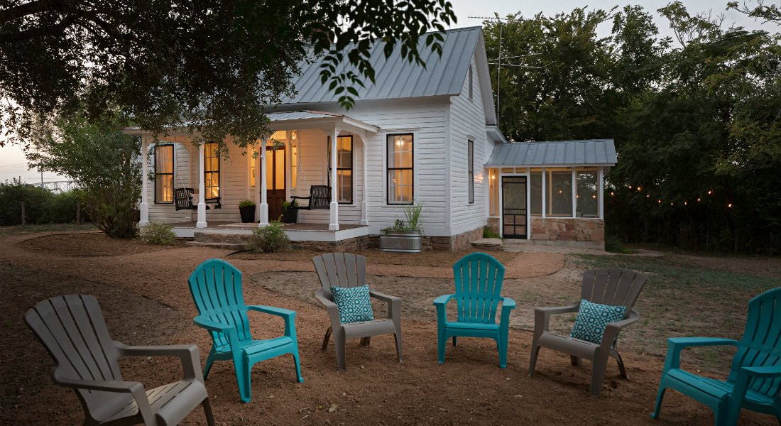 Blue and tan Adirondack chairs in the forefront of a white cottage with covered porch and attached screened porch