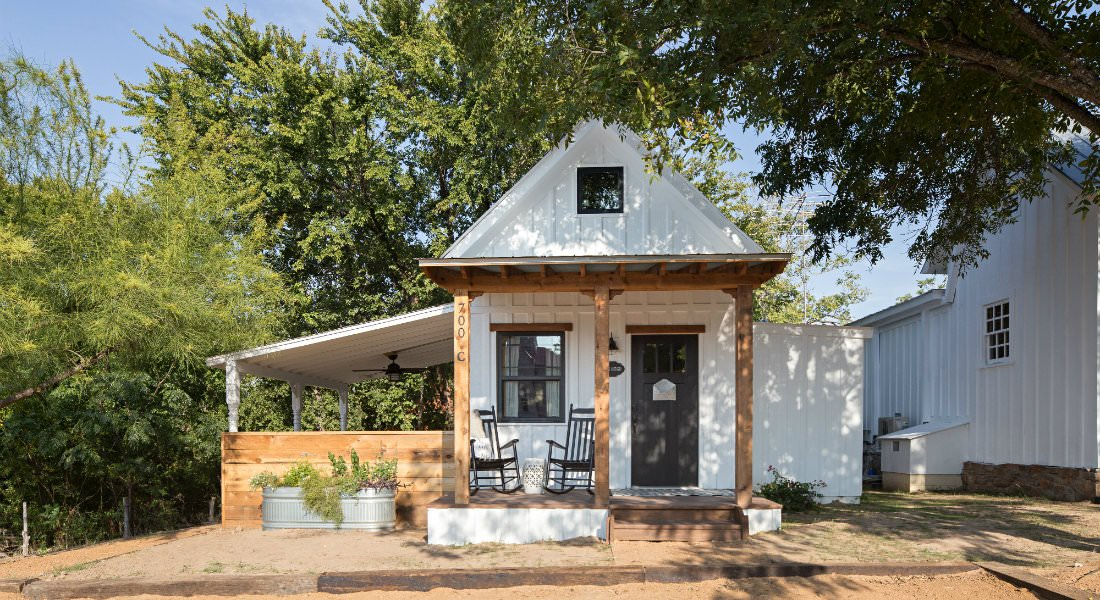 white cottage with covered front porch and covered side patio with privacy wall surrounded by trees