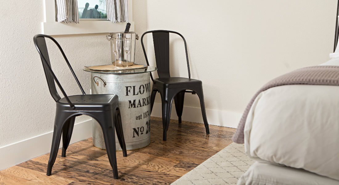 Close-up of vintage tin can table with glass top, two black chairs and hardwood floors