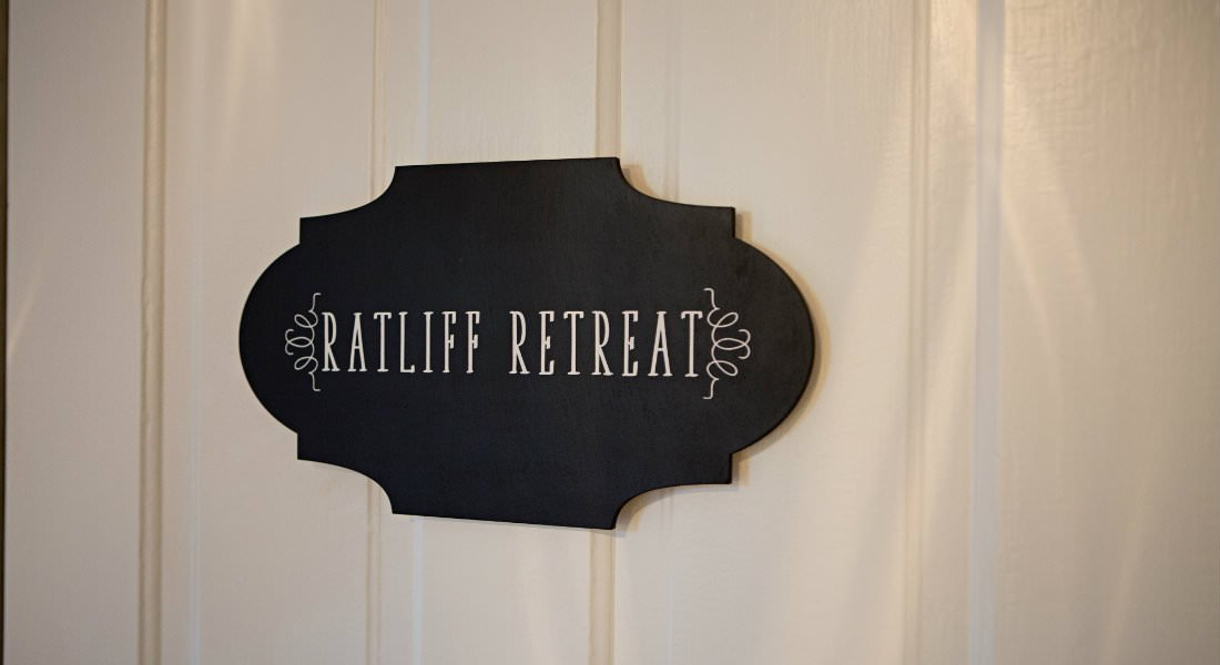 close-up view of black oval Ratliff Retreat sign