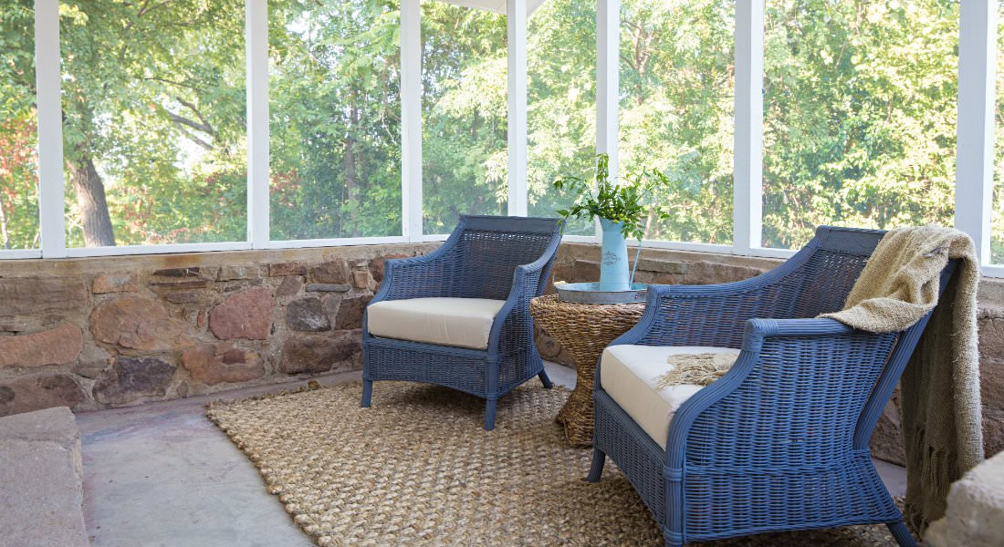 Screened porch with stone wall, and blue wicker chairs flanking a round wicker table
