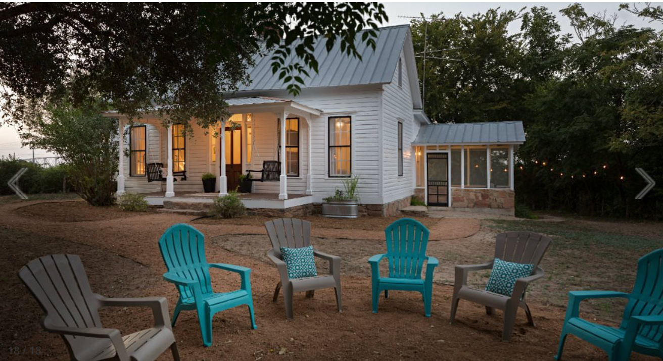 White cottage surrounded by trees with a circle of chairs out front