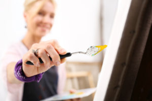 closeup of female artist with hand holding yellow paint on palette knife touching canvas on easel