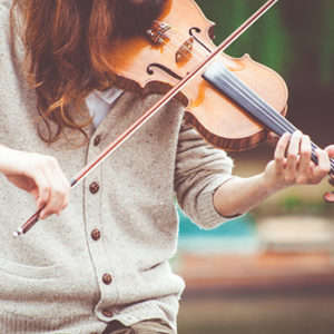 Torso of girl with long brown hair wearing beige sweater playing violin