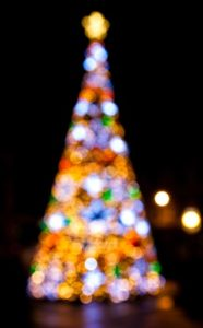 Blurred night exposure of multicolored lighted Christmas tree with gold star against black sky by Dawid Zawiła on Unsplash