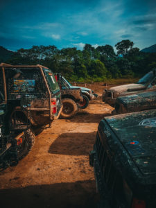 7 muddy jeeps parked in reddish brown dirt with trees in background