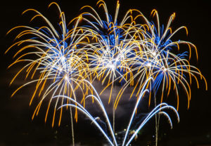 yellow blue and white fireworks display against an inky black sky
