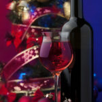 red wine in glass in front of glass cylinder with Christmas balls and swirling ribbons