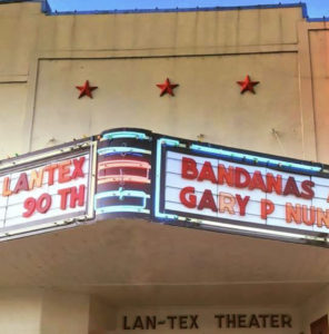 Lantex Theater with red stars on beige stucco facade and marquee with red letters