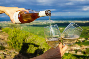 white wine pouring from brown bottle into two glasses that hand holds up against landscape