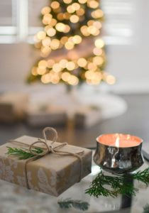 brown gift box beside stainless steel votive candle with out of focus christmas tree with white lights behind