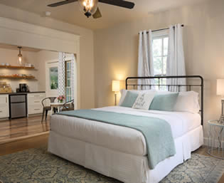 Beige room with white and turquoise bed and area rug on hardwood floors and glimpse of kitchenette in background