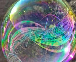 Close-up view of white bubble globe with iridescent colored reflection of bridge