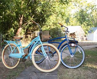 One light blue bicycle and one bright blue bicycle parked on a path with green trees in the background