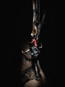 boy in shorts & backpack and boy in red shirt climbing through narrow cavern passage
