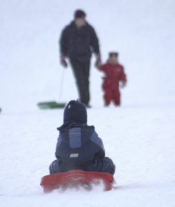 man pulling child on red sled in snow