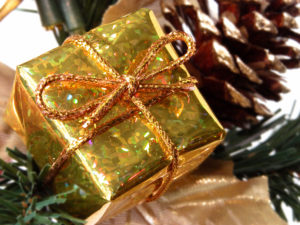 gold wrapped gift box in front of evergreen branches