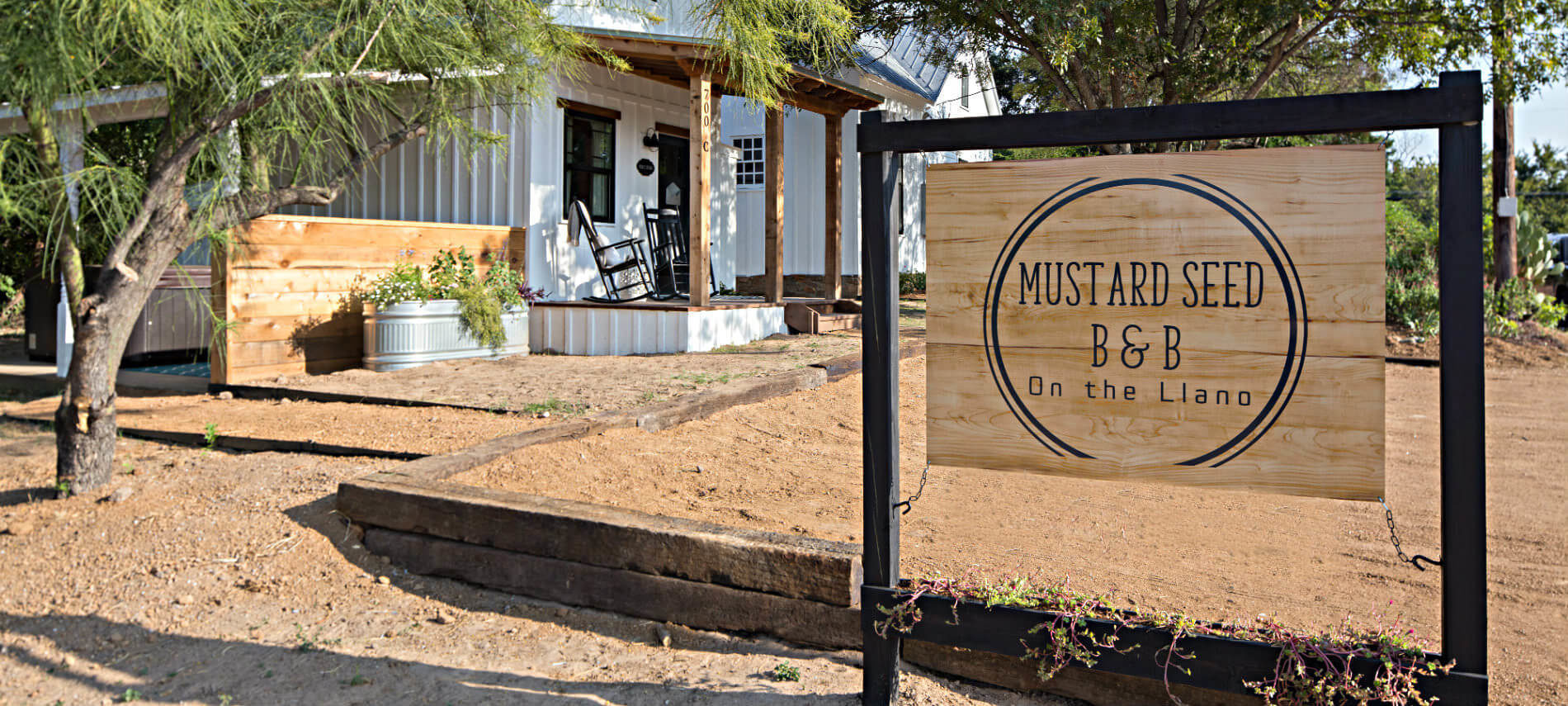 Rustic Mustard Seed B&B on the Llano sign with view of white cottages in the background
