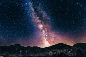 blue and white stars in Milky way rising over mountains