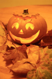 lighted Halloween carved smiling Jack O'Lantern with orange fall leaves
