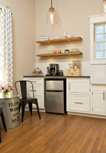 Off-white kitchenette with open wood shelving, wood floors, stainless steel mini fridge, small glass top table with two chairs