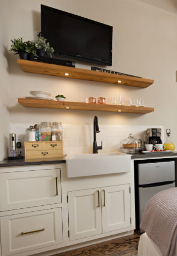 White kitchenette with mini fridge, open wood shelving with flat screen television