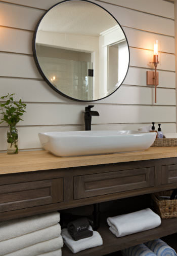Large rustic wood vanity with white vessel sink, oil-rubbed bronze faucet, round mirror, sconce light and shiplap