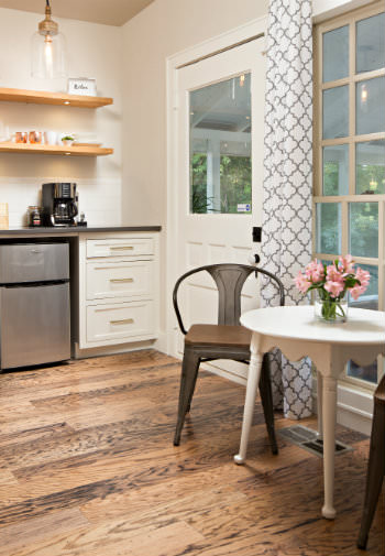 Beige kitchenette with wood floors, dinette table with two chairs, open shelving, and glass door to screened porch
