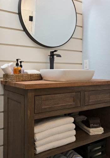 Rustic wood vanity with white vessel sink and round mirror in front of shiplap wall, white towels and toiletries