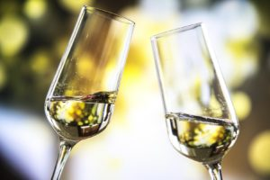 two flute glasses with white wine being toasted together